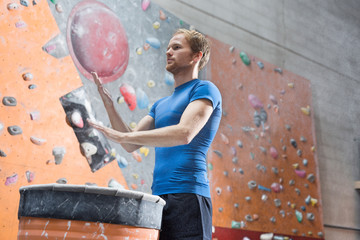 Low angle view of confident man dusting powder by climbing wall in crossfit gym