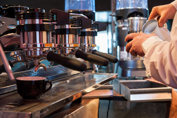 Preparing the coffee and cappuccino with professional espresso machine, at the bar