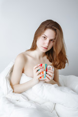 Portrait of pensive sad  beautiful young Caucasian girl woman with long  red hair sitting in bed wrapped covered with blanket, holiding cup, drinking coffee or tea, on white background.