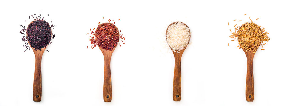 For different kind of raw rice in wooden spoon on white background