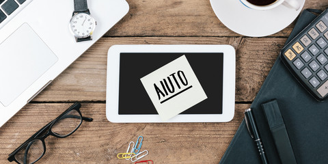 Aiuto, Italian text for Help , yellow sticky note, office desk with computer technology, high angle