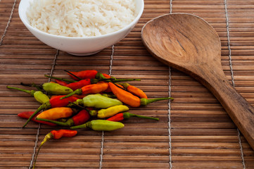 Jasmine rice in white bowl on bamboo wooden table with wood spoon and heap of colorful chili pepper