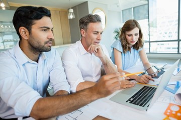 Architects discussing over laptop in conference room
