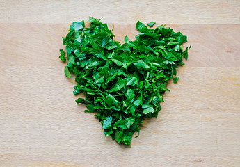Heart shape of green parsley on wooden background