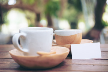 A business card and a cups of hot Latte coffee on vintage wooden table with blur  nature background