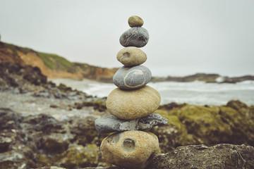 Stacked stones on rocks at beach against sky Fototapete