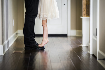 Low section of girl tiptoeing on father's feet at home