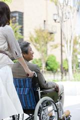 Mature woman pushing senior man on wheelchair