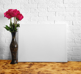 Mock up poster with a bouquet of flowers.  Empty canvas. White brick wall on background.