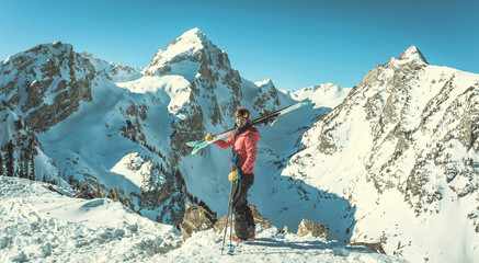 Portrait of happy female skier standing against snowcapped mountains