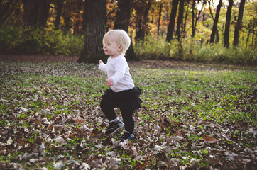 Side view of cute baby girl walking on grassy field