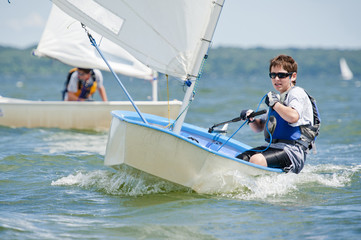 Boy sailing sailboat at sea