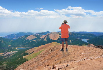 Man standing on top of mountain rock taking pictures, looking at beautiful summer mountains landscape, from Pikes Peak summit on hiking trip.  Pike Peak National Forest, Cascade, Colorado, USA