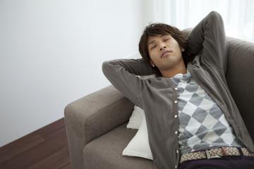 Young man lying on sofa sleeping