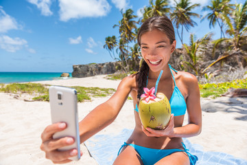 Happy girl taking selfie on summer beach vacation. Cute Asian multiracial bikini woman drinking fresh coconut water smiling holding mobile phone for self-portrait picture on tropical travel.