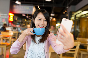 Woman taking selfie in coffee shop