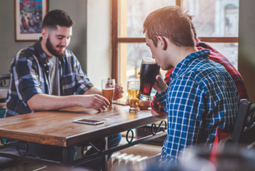 Group of Hipster Friends drinking beer and talking at the bar