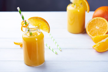 Fresh orange juice in the jar with straw on white wood table.