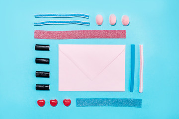 Group of tasty colorful sugar candies and blank paper envelope