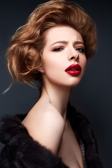 Young girl in a fur coat and bright makeup. Beautiful model with red lips and hairstyle. Photo is taken in a studio. Beauty of the face.