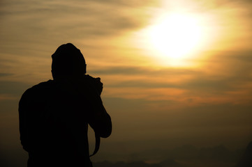 Silhouette of a photographer who shoots a sunrise in the mountain