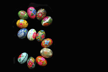 """One of the letters of the word """"Easter"""". Letters are made of Easter eggs, of different colors and with different patterns. On a black background"""