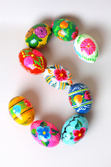 "One of the letters of the word ""Easter"". Letters are made of Easter eggs, of different colors and with different patterns. On a white background"