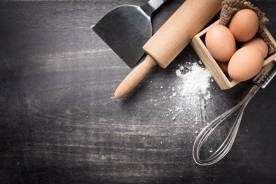 Ingredients for baking dough including flour, eggs, whisk and rolling pin on dark wooden background