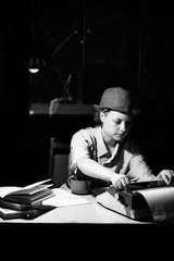 Portrait of a girl in a hat sitting at a table and typing on a typewriter at night
