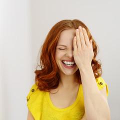 lachende frau hält eine hand vor ihr gesicht