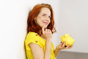 nachdenkliche frau hält ein gelbes sparschwein in der hand