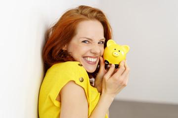 frau freut sich und hält ein kleines gelbes sparschwein in der hand