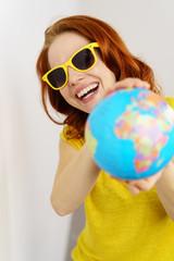 lachende frau mit sonnenbrille zeigt einen globus