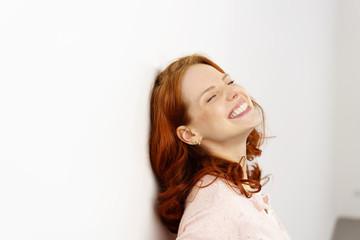 frau lehnt sich lachend an eine wand