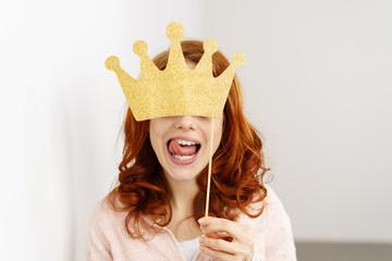frau versteckt sich hinter eine goldenen krone