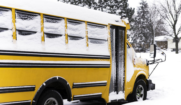 School bus parked in a residential neighborhood during a snow day while kids are home