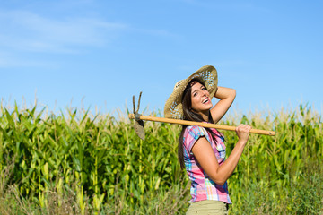 Successful farmer holding grubbing hoe against a green corn field. Agriculture farming and rural lifestyle concept.