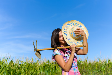 Joyful farmer holding grubbing hoe against a green corn field. Agriculture farming and successful rural lifestyle concept.