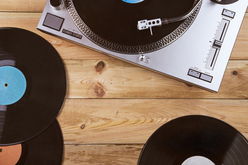 Gramophone with a vinyl record on wooden table, top view