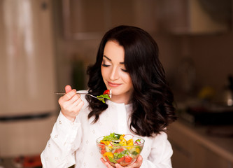 Smiling brunette woman eating salad with fresh vegetables in bowl at kitchen. Healthy lifestyle. 20s.
