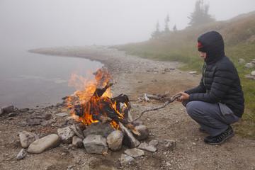 Young Boy Enjoying A Camp Fire Beside A Lake
