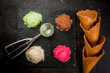 Selection of colorful home made ice cream: lemon (pistachio) green, berry pink, chocolate, white vanilla. With a spoon for balls, waffle cones, on a slate board, on a black table. Top view, copy space