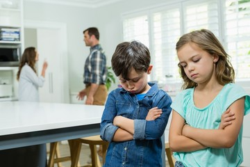 Sad siblings standing with arms crossed