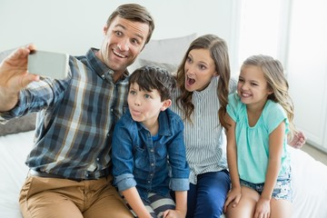 Smiling man taking selfie with family while sitting in bedroom