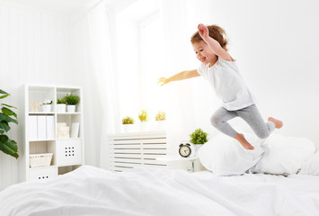 happy child girl  jumps and plays bed