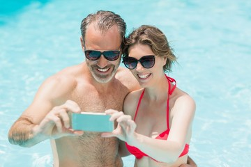 Happy couple taking selfie from mobile phone in pool