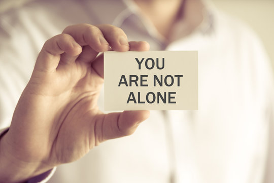 Businessman holding YOU ARE NOT ALONE message card