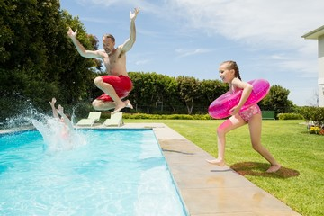 Happy father and daughter jumping in swimming pool