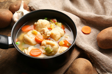 Stewpan with delicious chicken and dumplings on table