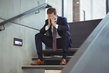 Depressed businessman sitting on stairs